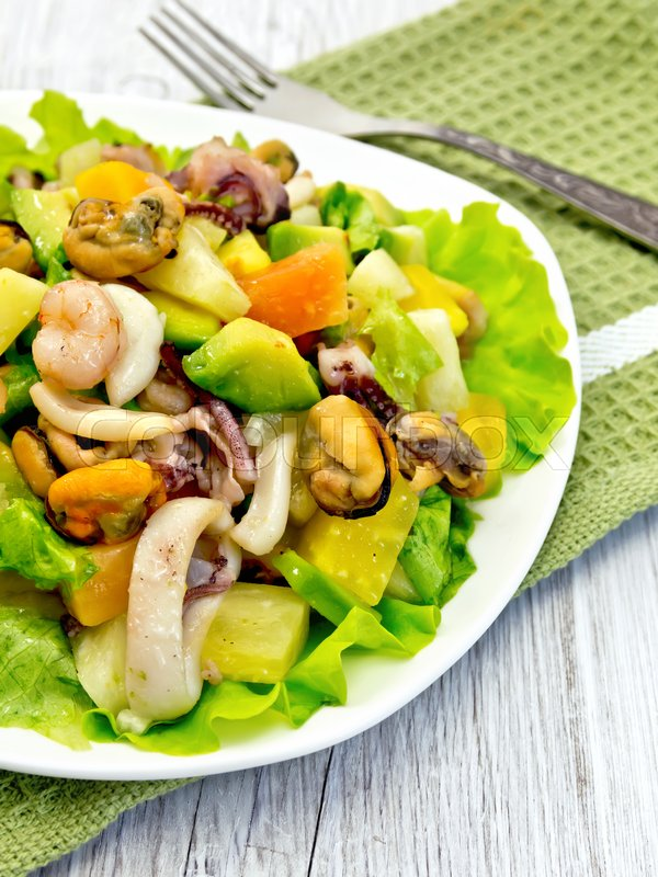 Stock image of 'Salad with shrimp, octopus, mussels and calamari with avocado, lettuce and pineapple in a plate on a napkin on a light wooden board'