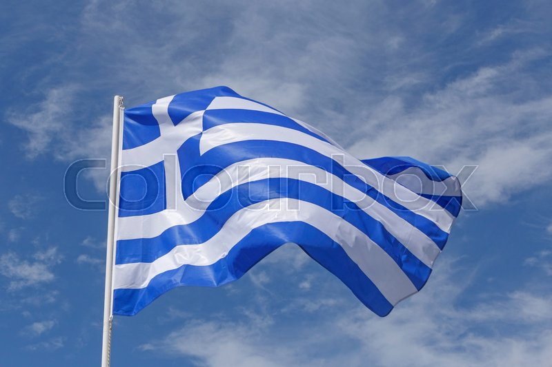 Stock image of 'Flag of Greece against blue sky with white clouds'