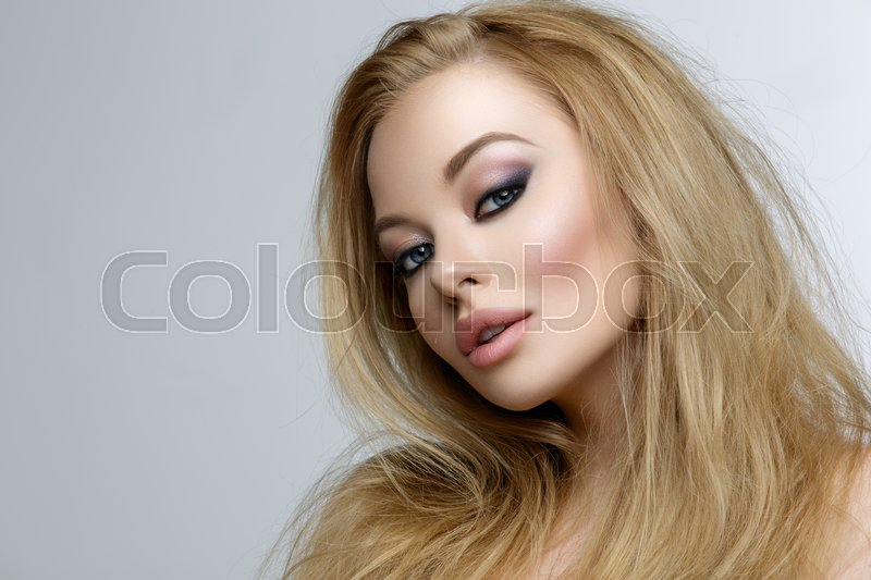 Stock image of 'Closeup portrait of beautiful young woman with messy long blond hair and bright makeup. Beauty shot over grey background.'