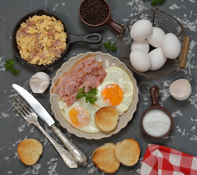 Stock image of 'Scrambled eggs with bacon on a gray background'