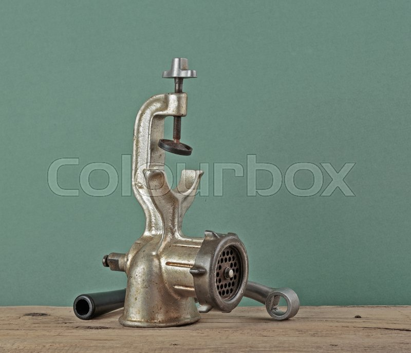 Stock image of 'Old manual meat grinder on a wooden table'