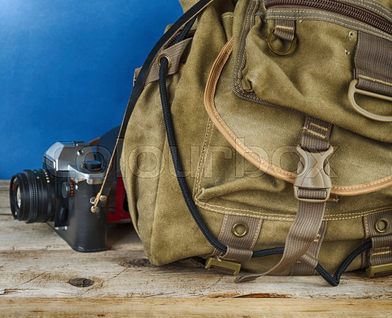 Stock image of 'Old travel backpack  and camera on the wooden floor'