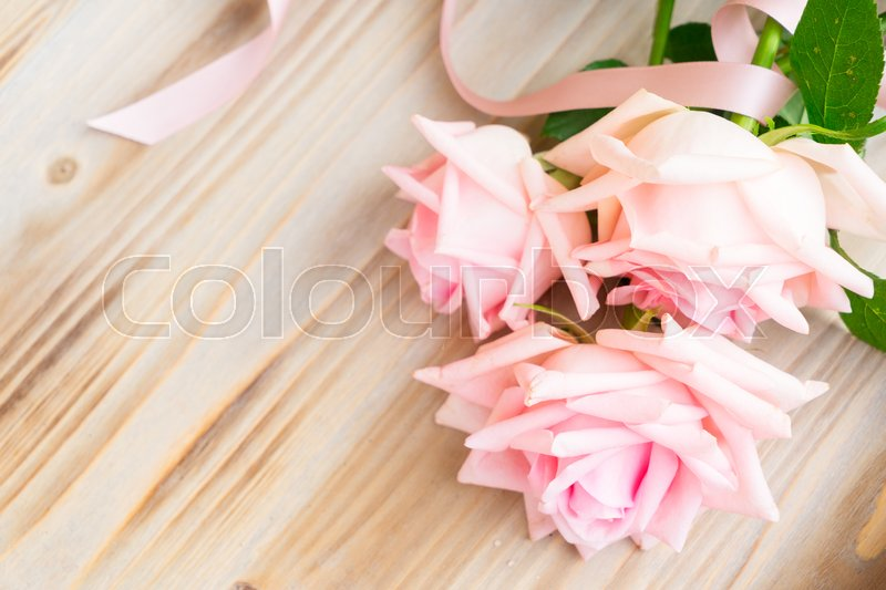 Stock image of 'Pink blooming fresh roses with ribbon on wood with copy space'