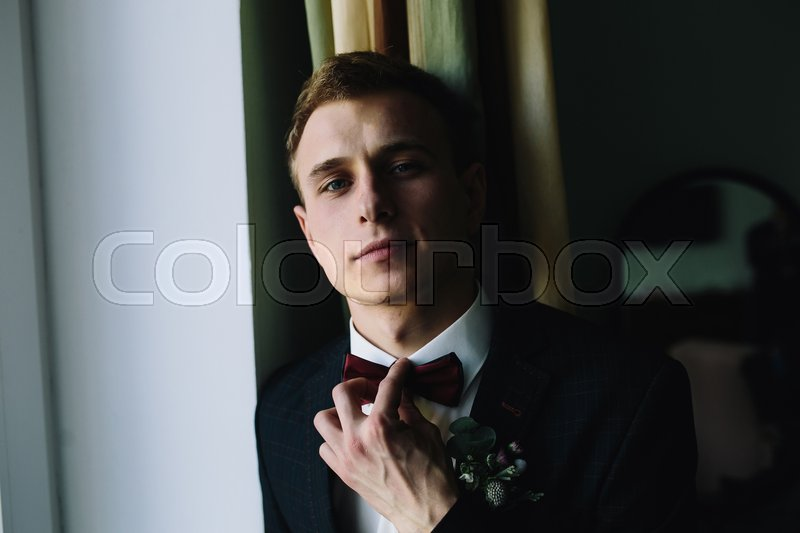 Stock image of 'groom standing at the window and posing for the camera'