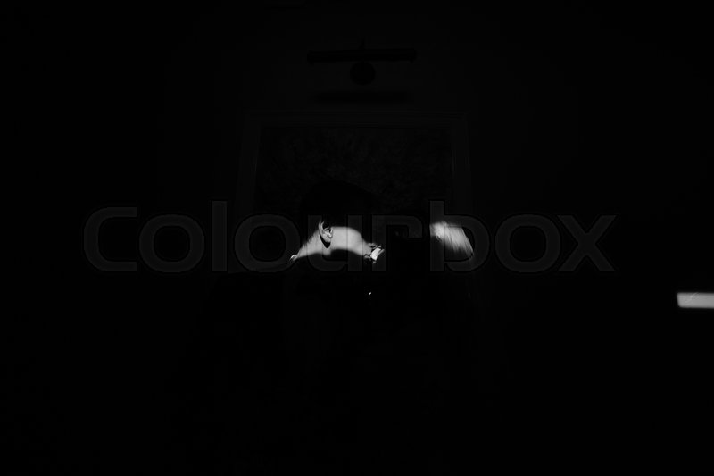 Stock image of 'bride and groom in a dark room, illuminated by light'