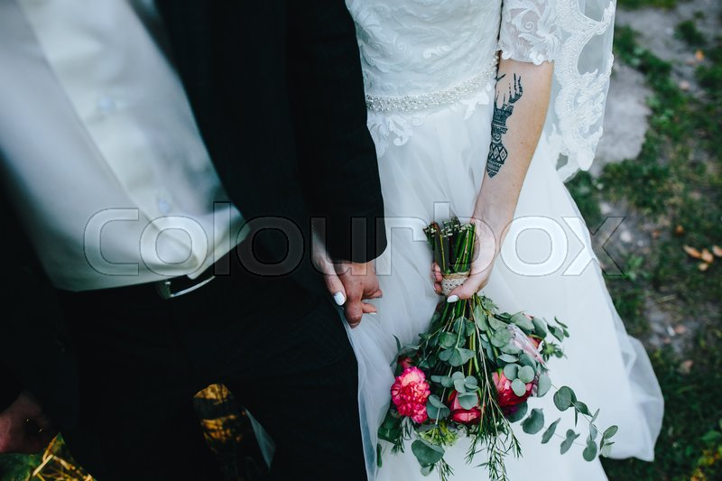 Stock image of 'bride and groom holding hands and posing for the camera, close view'
