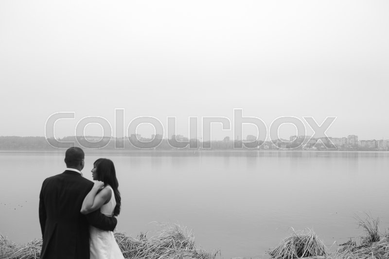 Stock image of 'Wedding couple posing on a lake shore'