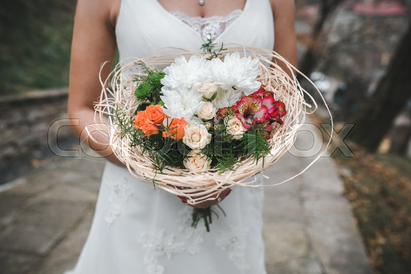 Stock image of 'Bride holding wedding bouquet in her hands, close view'