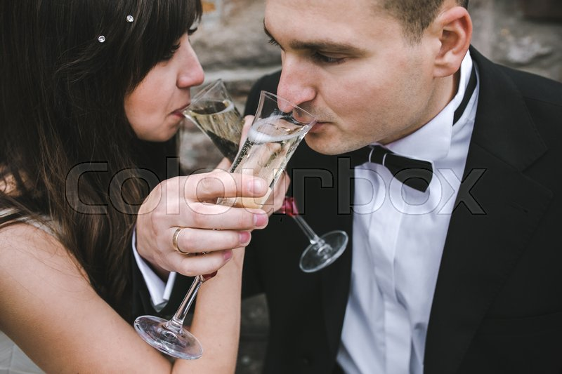 Stock image of 'Beautiful wedding couple at a picnic under a tree drinking champagne'