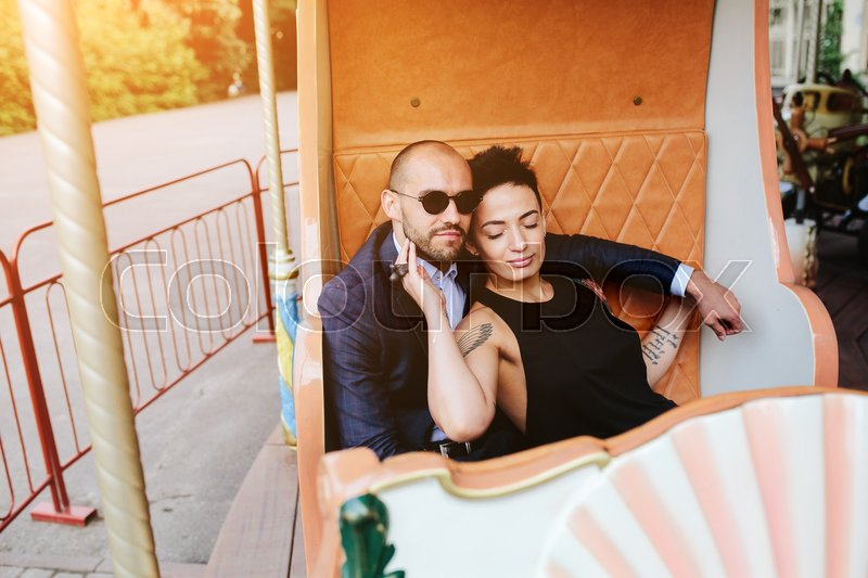 Stock image of 'adult man and woman on merry go round carousel'