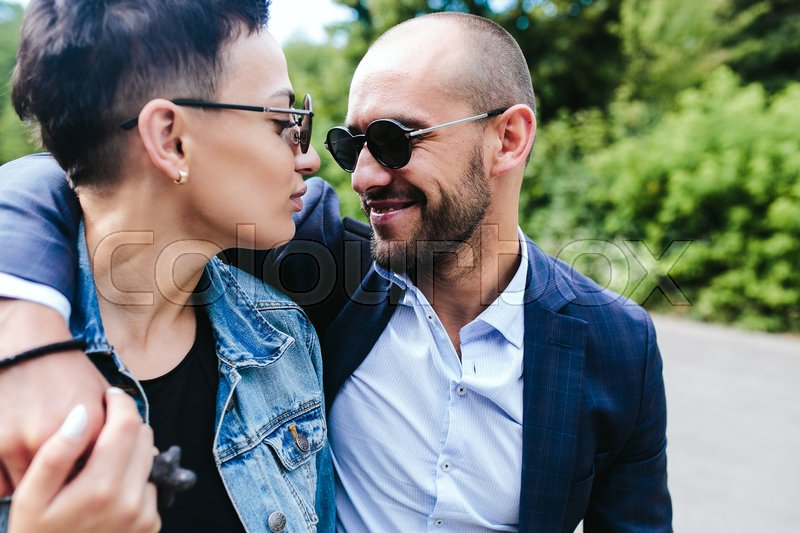 Stock image of 'Man and woman looking at each other and walk in an embrace'