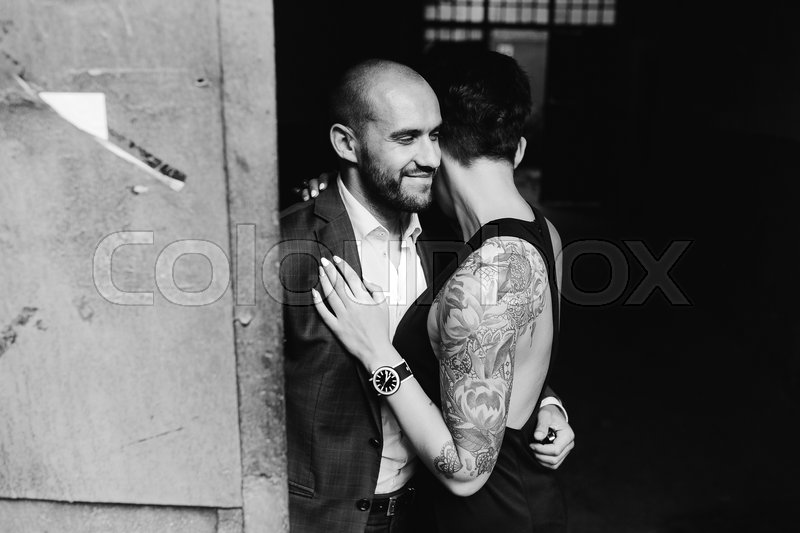 Stock image of 'man and woman hugging in the doorway of an abandoned building'