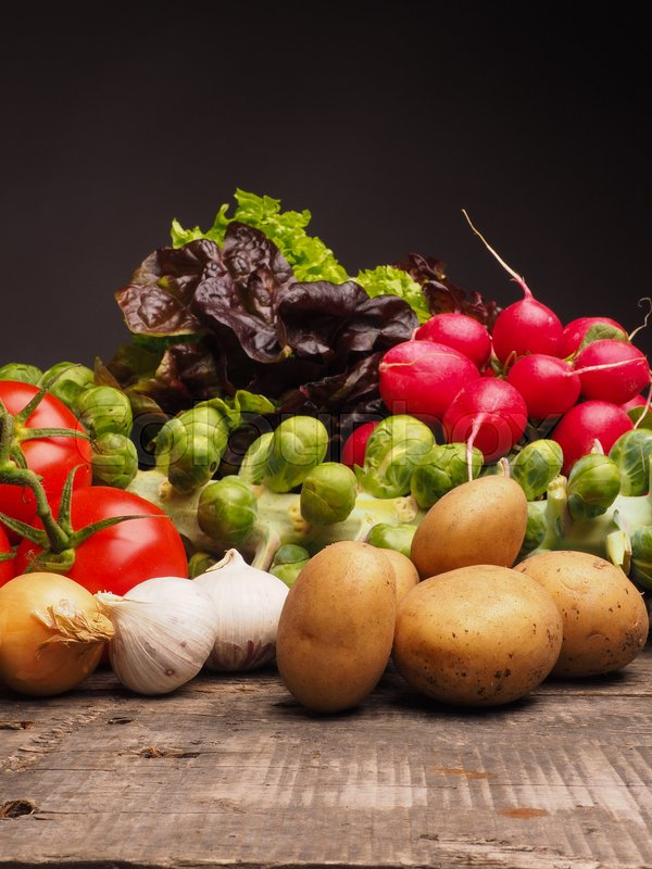 Stock image of 'Fresh organic vegetables on a wooden table, selective focus on the foreground'
