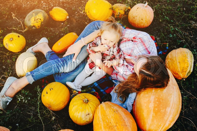 Stock image of 'mother and daughter lie between pumpkins on the field, Halloween eve'