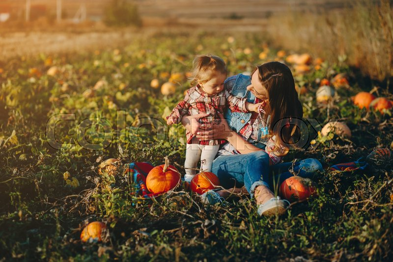 Stock image of 'mother and daughter on a field with pumpkins, Halloween eve'