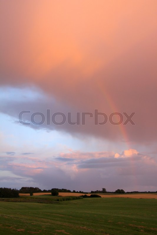 Stock image of 'Squall clouds and a rainbow in summertime'