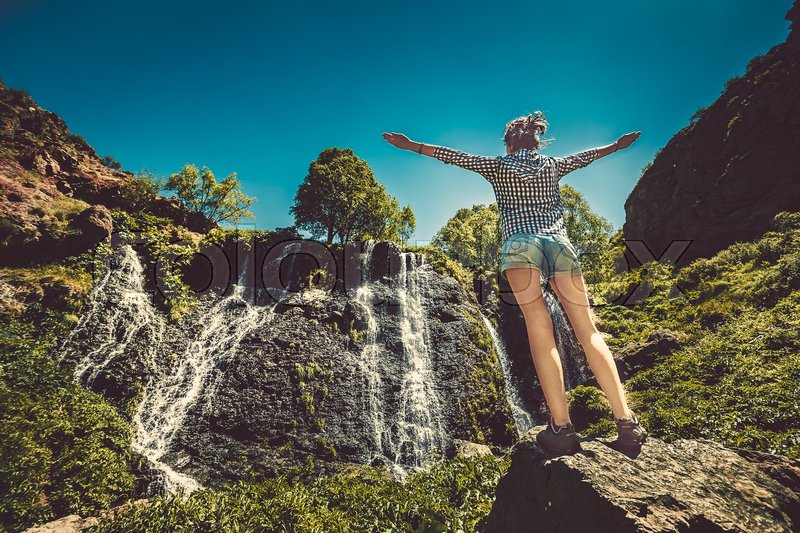 Stock image of 'Rear view of beautiful girl standing on background of mountain waterfall. Exploring Armenia'