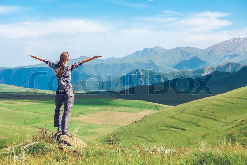 Stock image of 'Rear view of woman with raised hands on background of green hills and blue sky with clouds. Exploring Armenia'