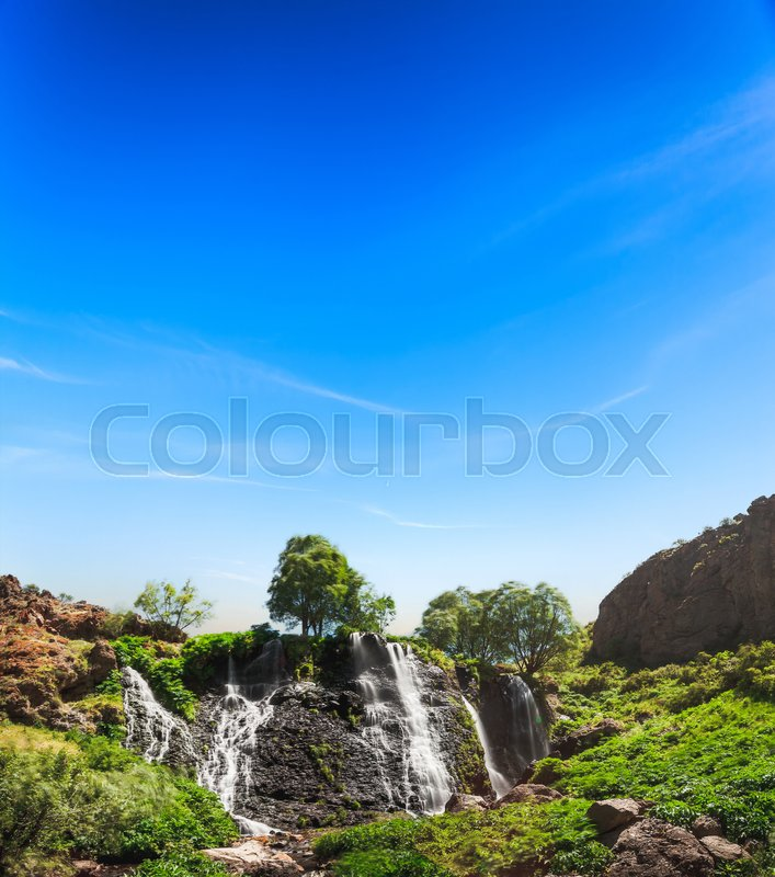 Stock image of 'View of beautiful mountain waterfall with blue sky on background. Exploring Armenia'