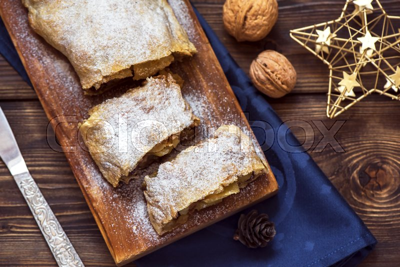 Stock image of 'Christmas homemade pastry. Apple strudel (pie) with raisins, walnuts and powdered sugar with Christmas decor close up.'