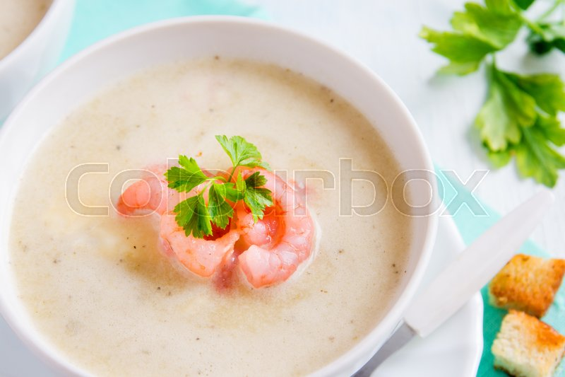 Stock image of 'Vegetable cream soup with shrimps and croutons in white bowl close up'