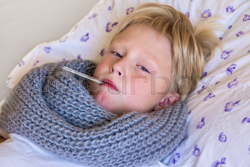 Stock image of 'Sick little boy holding thermometer laying in bed with sad face - healthcare and medicine concept'