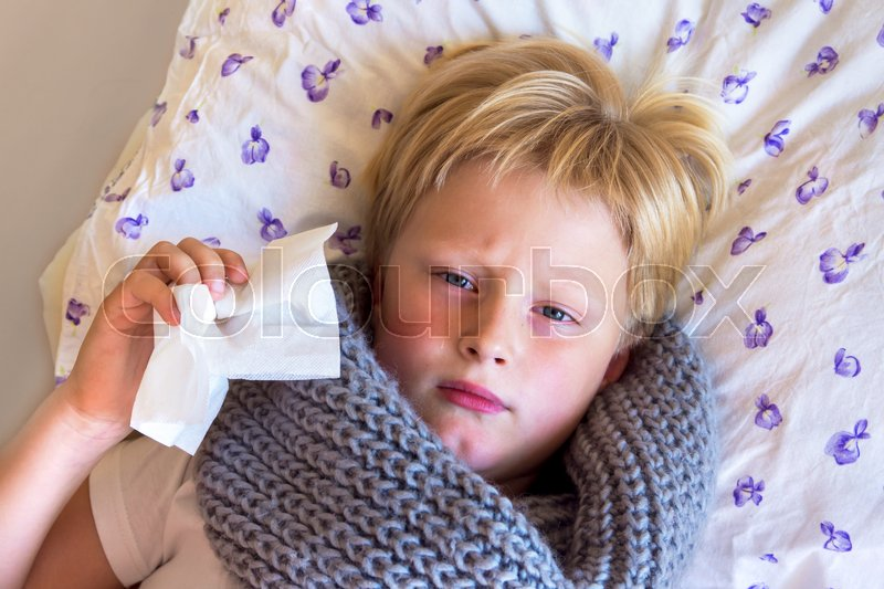 Stock image of 'Sick little child boy blowing nose laying in bed with sad face - healthcare and medicine concept'
