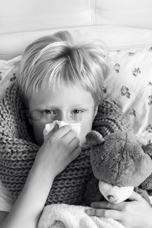 Stock image of 'Sick child (blond boy, kid) lying in bed with teddy bear and blowing his nose'