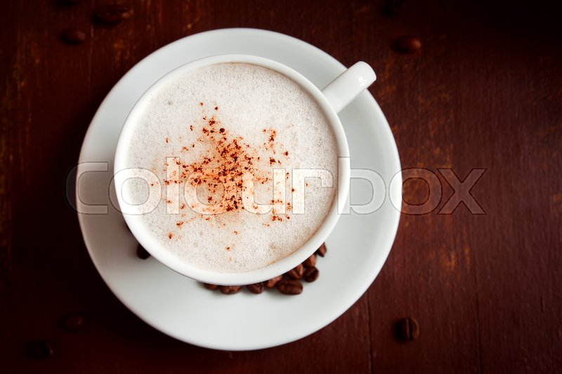 Stock image of 'Cup of cappuccino coffee with cacao topping over dark rustic wooden background '