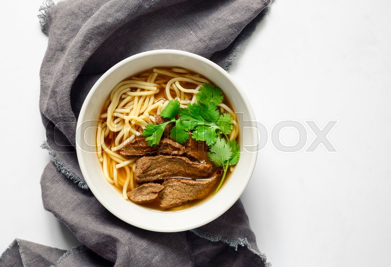 Stock image of 'Noodles and beef in a bowl, asian meal, top view'