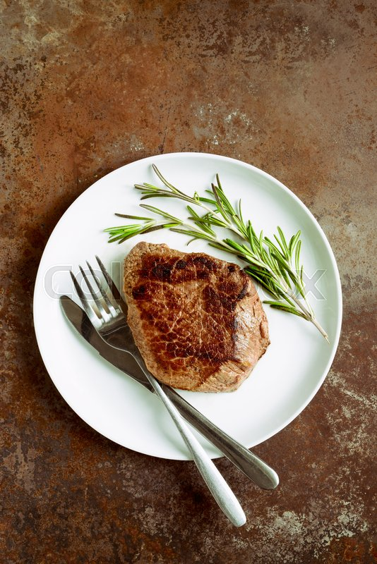 Stock image of 'Beef steake with rosemary served in a white plate, view from above'