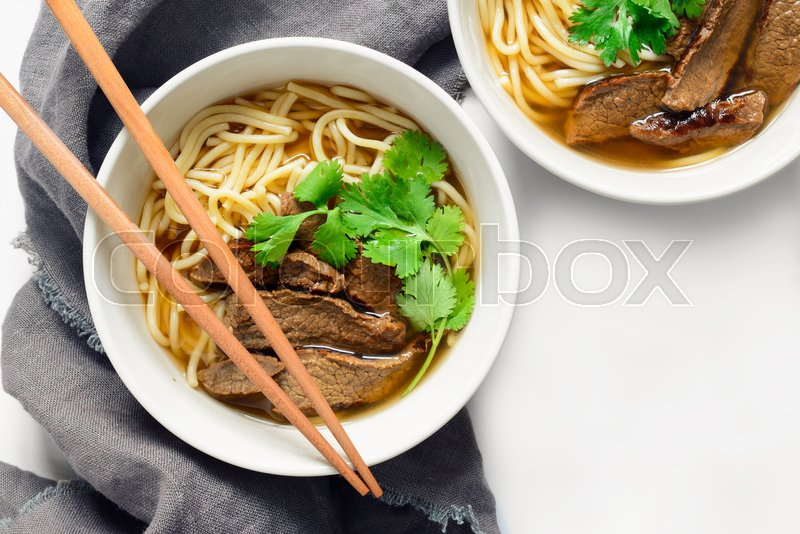 Stock image of 'Noodles and beef in two bowls, asian meal, top view'