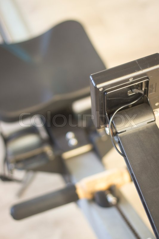 Stock image of 'Gym exercise rowing machine static rower in gymnasium fitness studio.'
