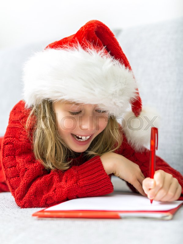 Stock image of 'Happy little girl in red hat writing a letter to Santa Claus.'