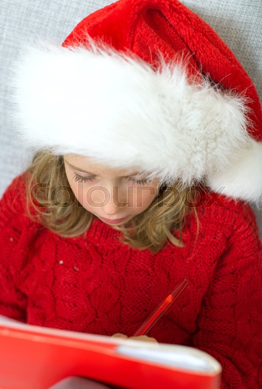 Stock image of 'Little girl in red hat writing a letter to Santa Claus.'