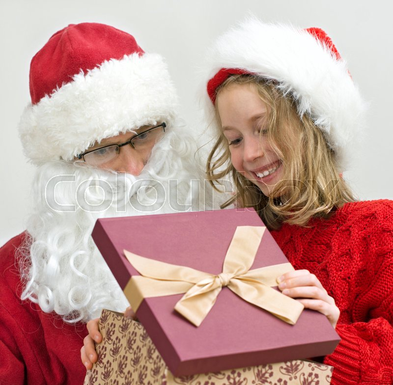 Stock image of 'Santa Claus is giving present to little girl at Christmas.'