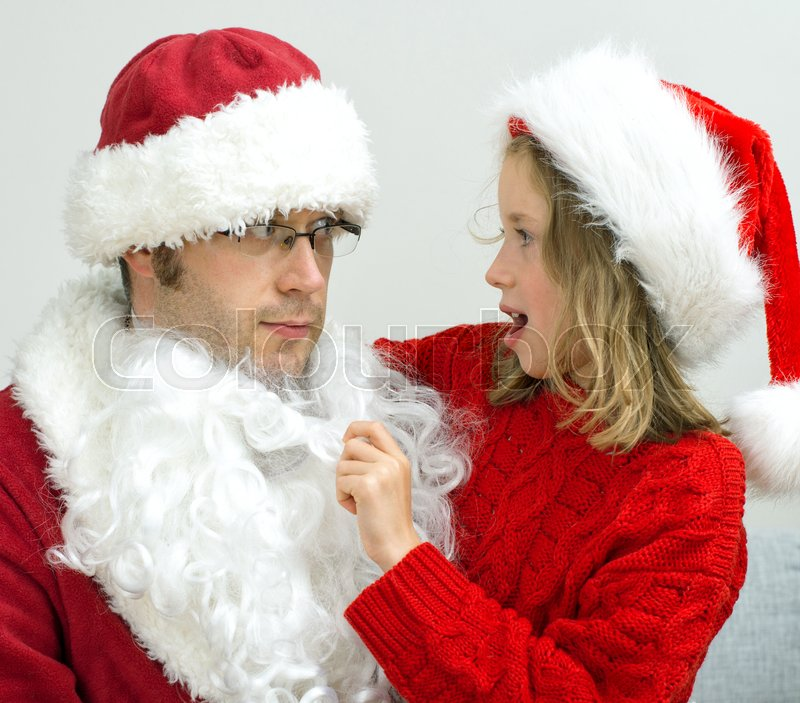 Stock image of 'Surprised little girl looking at fake Santa Claus.'