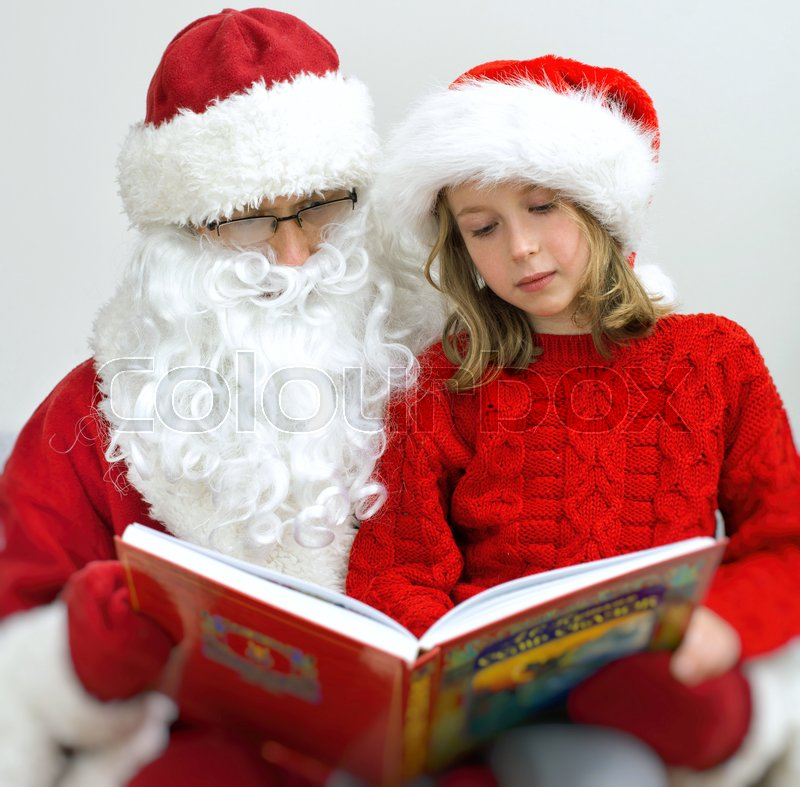 Stock image of 'Santa Claus and little girl reading fairy tales at Christmas.'