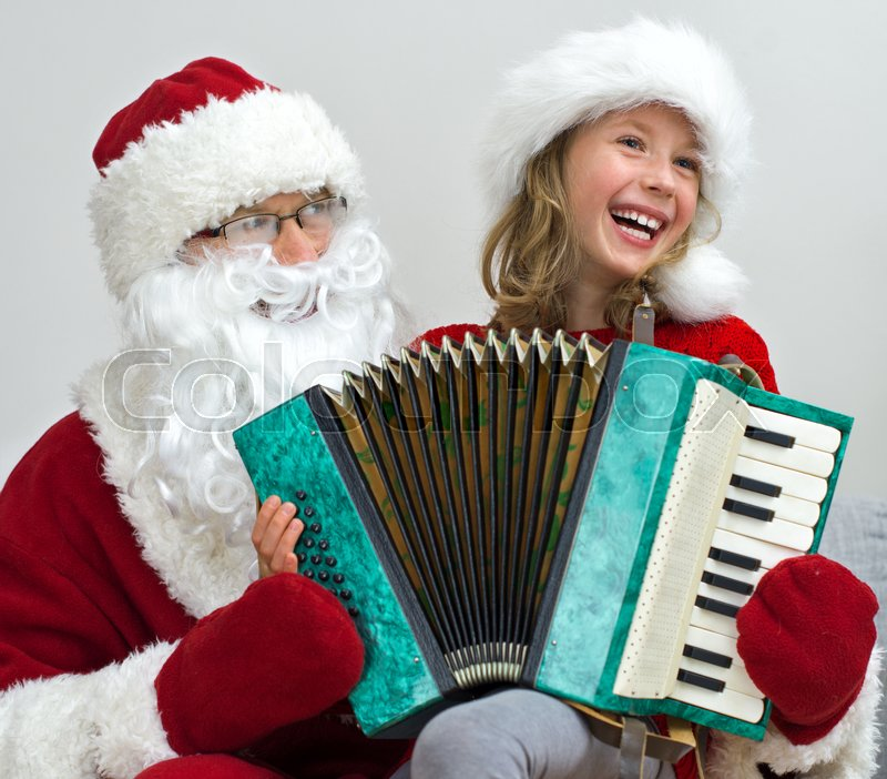 Stock image of 'Santa Claus and little girl playing accordion at Christmas.'