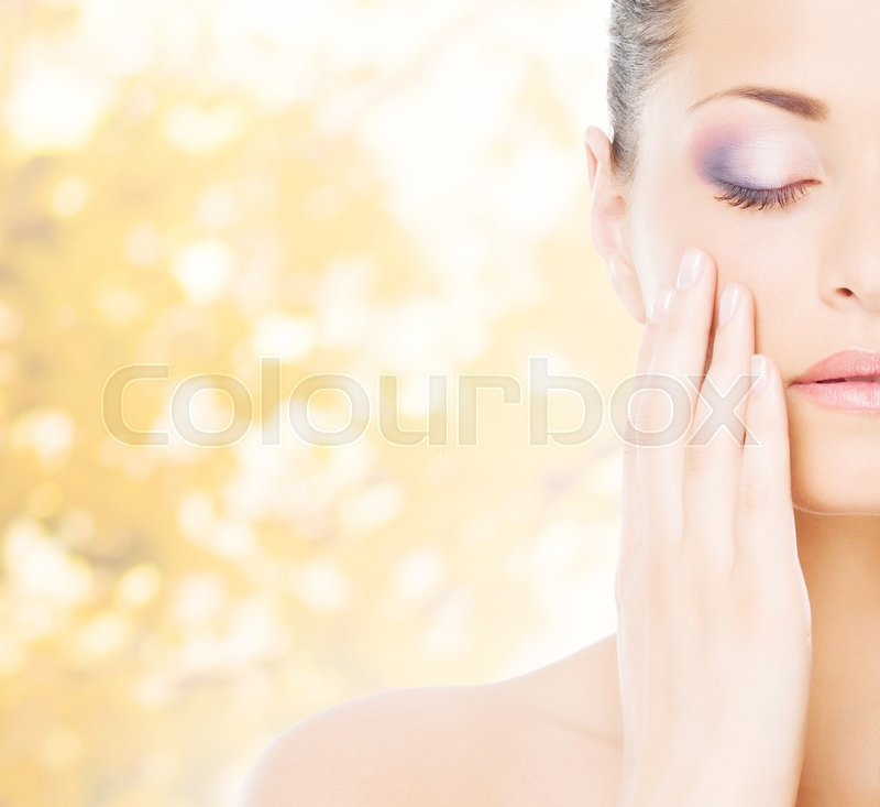 Stock image of 'Portrait of young, natural and healthy woman over yellow autumn background.'