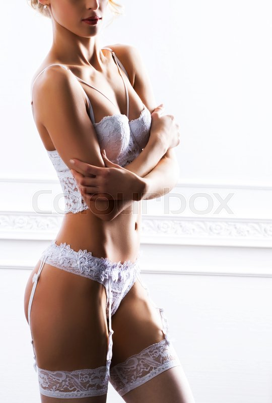 Stock image of 'Close-up photo of young and sexy bride in underwear and stockings. Woman in bridal underwear. Vintage retro background.'