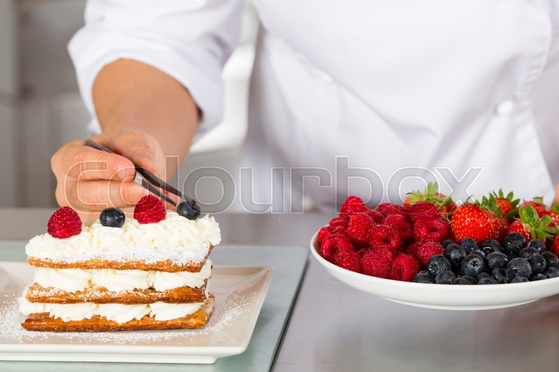 Stock image of 'Pastry chef decorating with berries pie pastry'