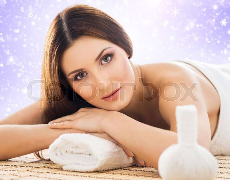 Stock image of 'Young, healthy and beautiful girl relaxing in winter spa salon. Massage therapy, healing medicine and health care concept. Christmas background.'