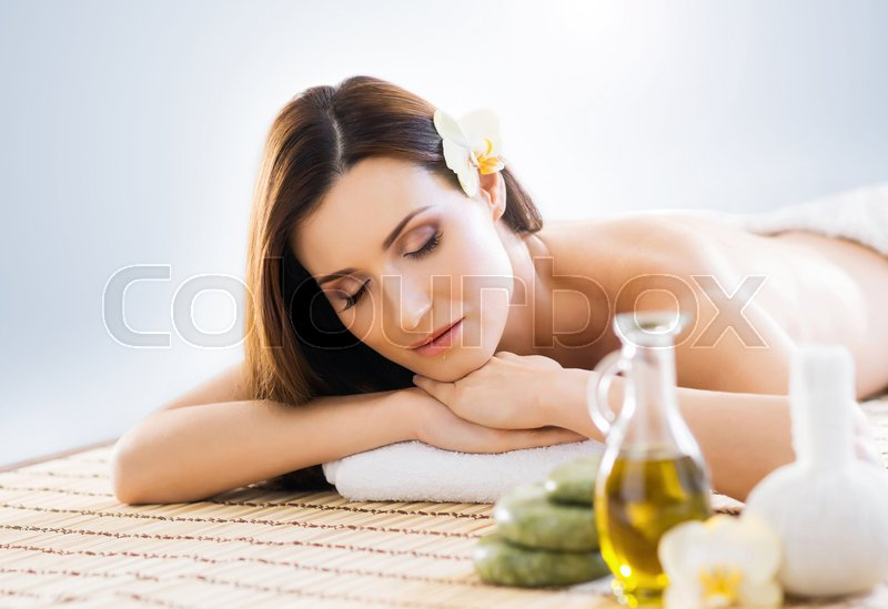 Stock image of 'Young and beautiful girl relaxing in Christmas spa salon. Massage therapy, healing medicine and health care concept. '