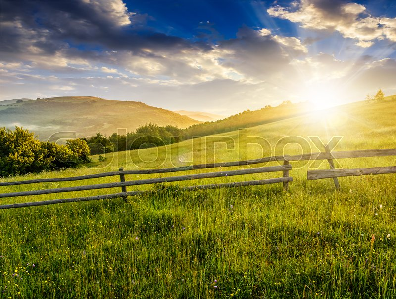 Stock image of 'wooden fence on agricultural grassy meadow with trees on hillside in Carpathian mountains at sunrise'