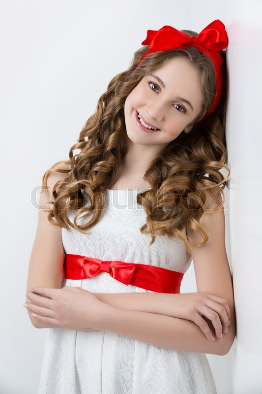 Stock image of 'Beautiful teenage girl with long curly hair and red ribbon bow on head wearing white dress. Happy expression. Studio portrait on white background. Copy space.'
