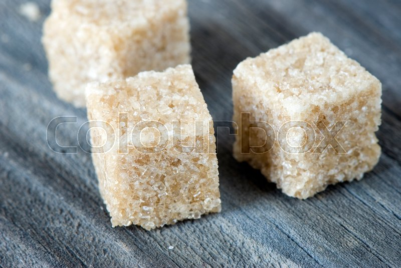 Stock image of 'pieces of cane sugar on a wooden board'