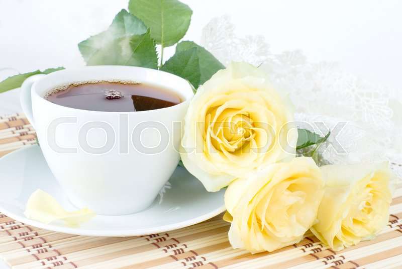 Stock image of 'cup of morning tea, a bouquet of yellow roses and vintage lacy doily on white background'