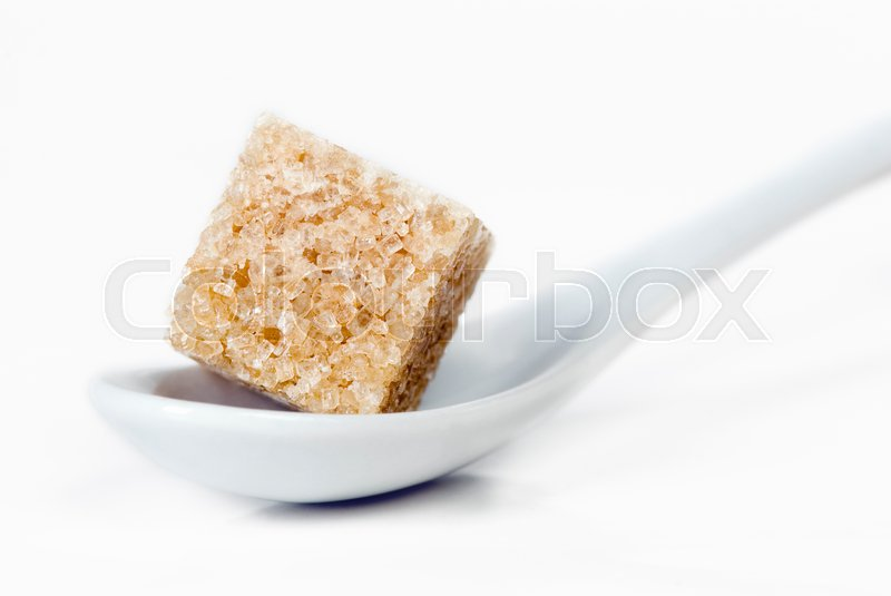 Stock image of 'a piece of cane sugar in a porcelain spoon'
