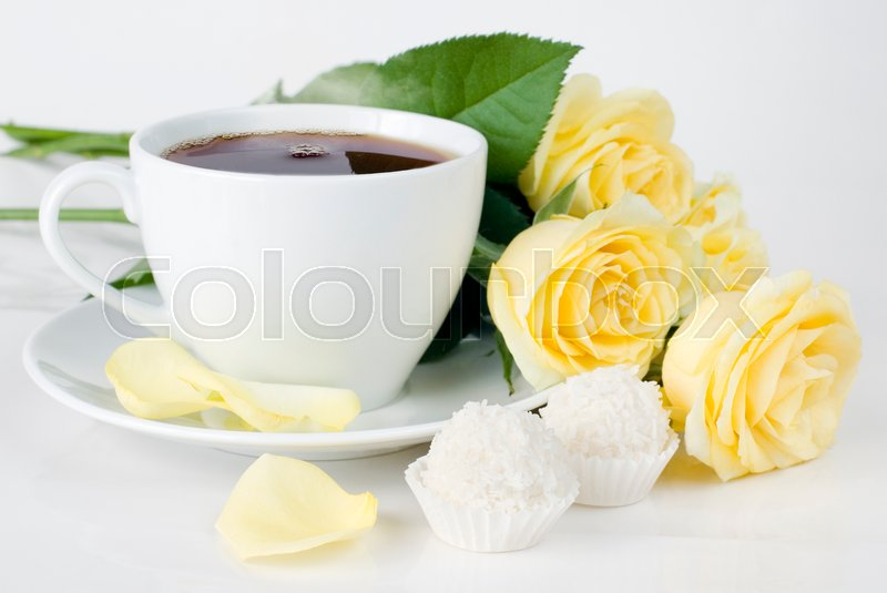 Stock image of 'cup of morning tea, two candy with coconut flakes and a bouquet of yellow roses'
